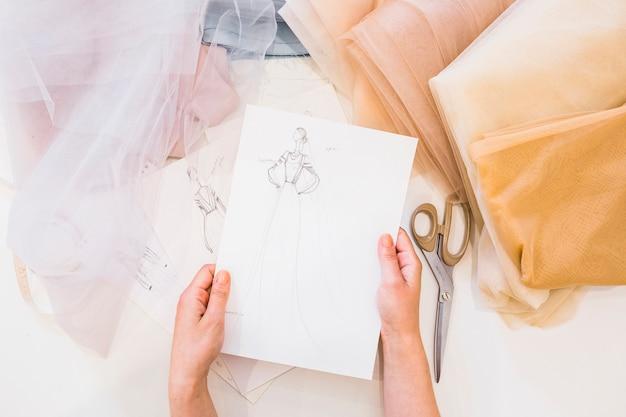 Obenliegende ansicht der hand des designers, die modeskizze über arbeitsplatz hält