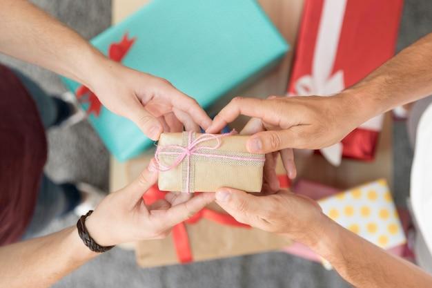 Obenliegende ansicht der hand des mannes die eingewickelte geschenkbox halten