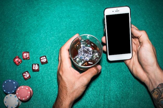 Obenliegende ansicht der hand des mannes, die mobiltelefon- und whiskyglas über der pokertabelle hält
