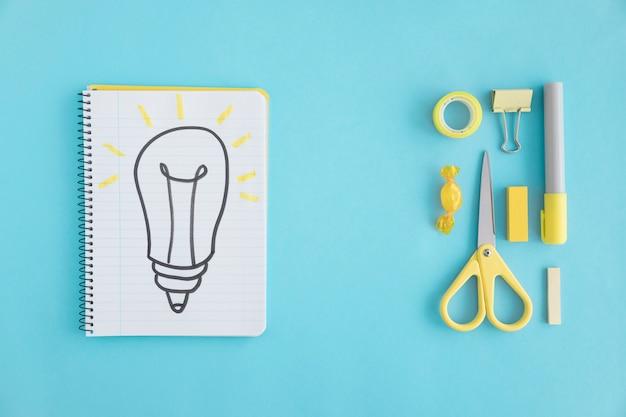 Obenliegende ansicht der hand gezeichneten glühlampe auf notizbuch mit stationärem auf blauem hintergrund