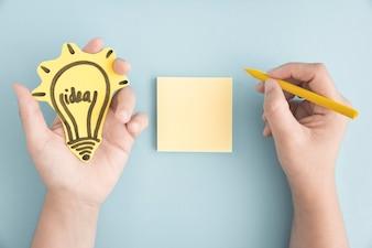 Obenliegende Ansicht der Hand Ideenblumeschreiben mit gelbem Zeichenstift auf klebriger Anmerkung über dem grauen Hintergrund halten