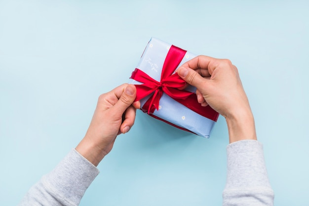 Obenliegende ansicht der hand roten bandbogen auf geschenkbox über blauem hintergrund binden