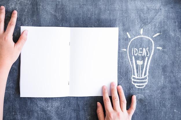 Obenliegende ansicht der hand weiße karte nahe der gezogenen ideenbirne auf tafel halten