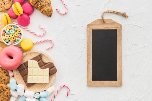 Obenliegende ansicht der hölzernen schiefermarke und der süßen nahrungsmittel auf weißem hintergrund