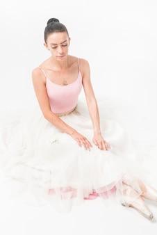 Obenliegende ansicht der jungen ballerina sitzend auf weißem hintergrund