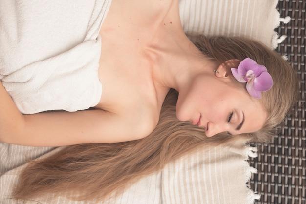 Obenliegende ansicht der jungen frau schlafend auf ruhesessel mit orchideenblume in ihrem kopf