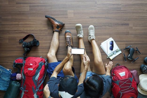 Obenliegende ansicht der jungen paarplanung des reisenden mit dem halten des intelligenten telefons