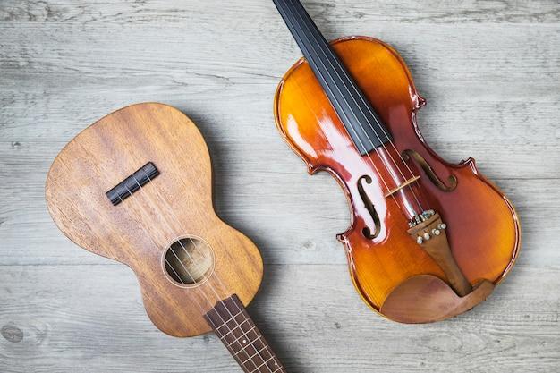 Obenliegende ansicht der klassischen gitarre und der violine auf hölzernem hintergrund