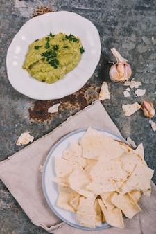 Obenliegende Ansicht der köstlichen mexikanischen Tortilla mit Guacamole über rostigem verwittertem Hintergrund