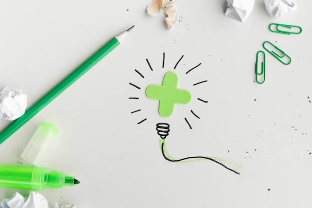 Obenliegende ansicht der kreativen hand gezeichneten glühlampe mit briefpapierprodukt auf weißer oberfläche