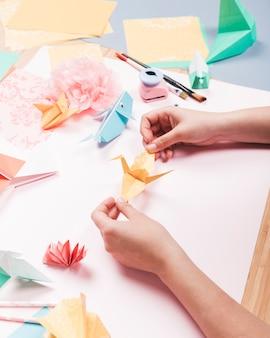 Obenliegende ansicht der menschlichen hand origamivogel über tabelle halten