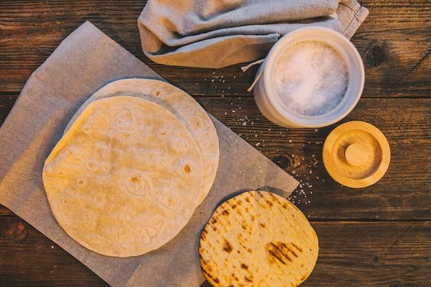 Obenliegende ansicht der mexikanischen tortilla des köstlichen weizens auf tabelle mit glas zucker