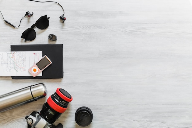 Obenliegende ansicht der verschiedenen reisenden ausrüstung auf hölzernem schreibtisch