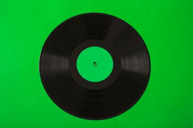 Obenliegende ansicht der vinylaufzeichnung auf grünem hintergrund