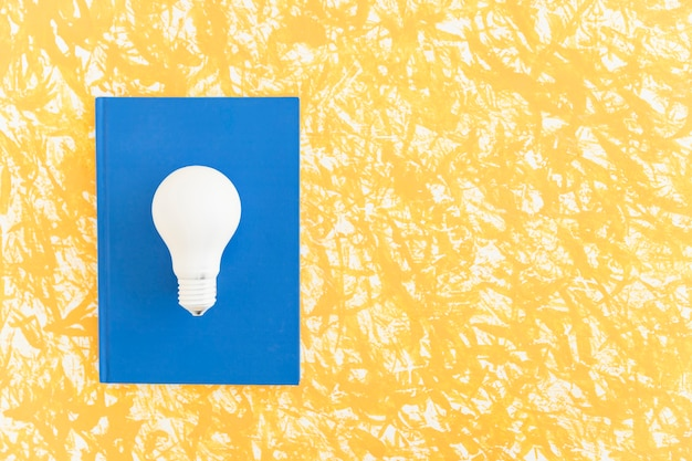 Obenliegende ansicht der weißen glühlampe auf blauem notizbuch über dem musterhintergrund