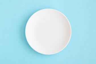 Obenliegende Ansicht der weißen leeren Platte auf blauem Hintergrund