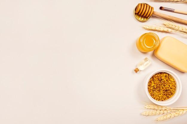 Obenliegende ansicht der weizenähren; bienenpollen; ätherisches öl; seife; honig; honigschöpflöffel und make-up pinsel
