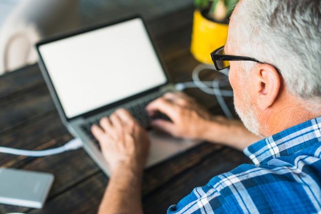 Obenliegende ansicht des älteren mannes arbeitend an laptop