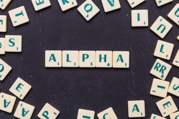 Obenliegende ansicht des alphatextes auf scrabble-buchstaben über schwarzem hintergrund