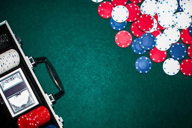 Obenliegende ansicht des aluminiumkoffers mit poker stellte auf schürhakentabelle ein