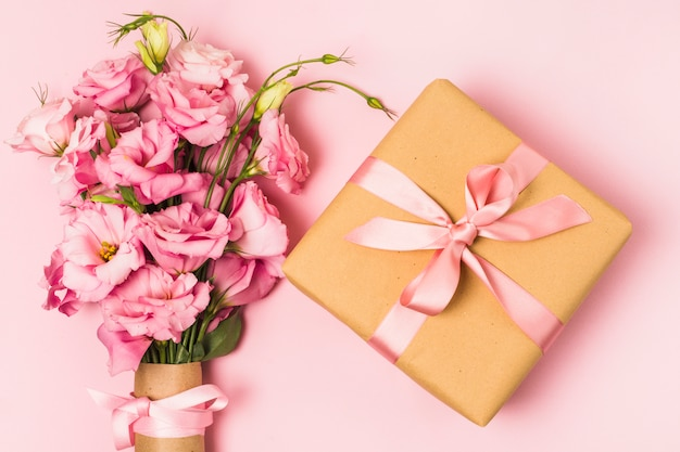 Obenliegende ansicht des blumenstraußes der frischen blume und der eingewickelten dekorativen geschenkbox