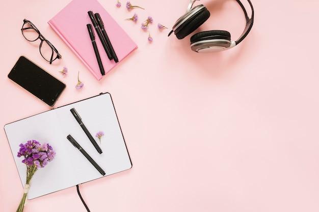 Obenliegende ansicht des briefpapiers mit kopfhörer und mobiltelefon auf rosa hintergrund