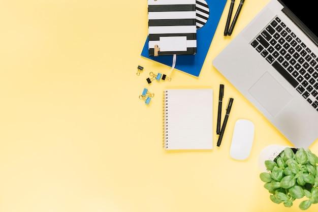 Obenliegende ansicht des briefpapiers mit laptop und maus auf papiergelbhintergrund