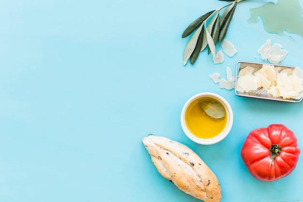 Obenliegende ansicht des brotes, des öls, des geriebenen käses und der tomate auf blauem hintergrund