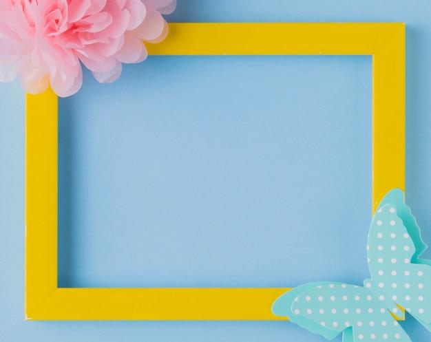 Obenliegende ansicht des dekorativen gelben fotorahmens mit blumen- und schmetterlingsausschnitt