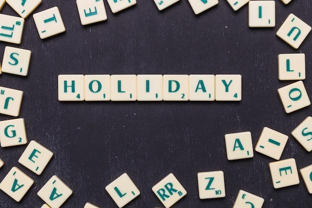 Obenliegende ansicht des feiertagstextes auf scrabblebuchstaben über schwarzem hintergrund