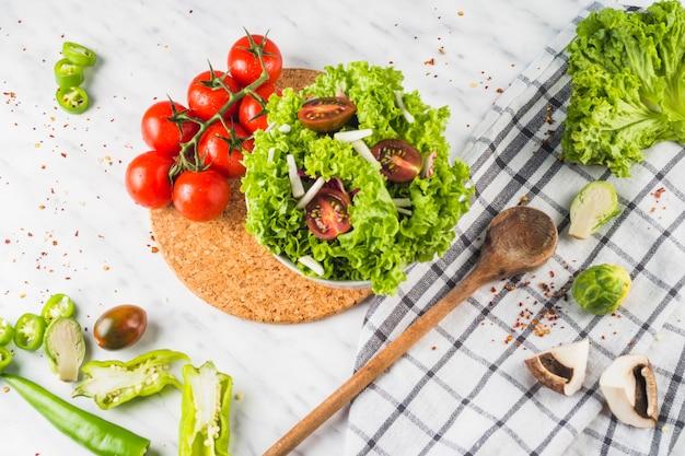 Obenliegende ansicht des frischen grünen salats mit tomate und pilz