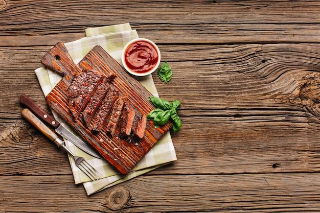 Obenliegende ansicht des gebratenen steaks mit basilikumblättern und -soße auf hölzernem schreibtisch