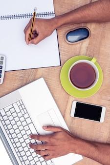 Obenliegende ansicht des geschäftsmannes arbeitend an laptop beim schreiben auf buch am schreibtisch im büro