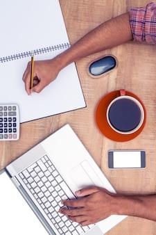 Obenliegende ansicht des geschäftsmannes arbeitend im büro am schreibtisch