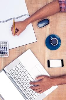 Obenliegende ansicht des geschäftsmannschreibens auf buch beim arbeiten an laptop im büro