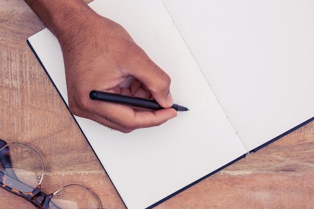 Obenliegende ansicht des geschäftsmannschreibens auf notizbuch durch brillen am schreibtisch im büro