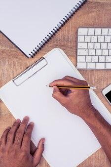 Obenliegende ansicht des geschäftsmannschreibens auf notizbuch durch computertastatur am schreibtisch im büro