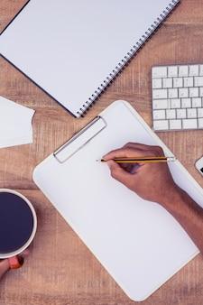 Obenliegende ansicht des geschäftsmannschreibens auf notizbuch durch kaffee am schreibtisch im büro