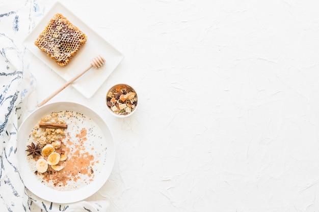 Obenliegende ansicht des gesunden frühstücks der hafer und dryfruits auf strukturiertem weißem hintergrund