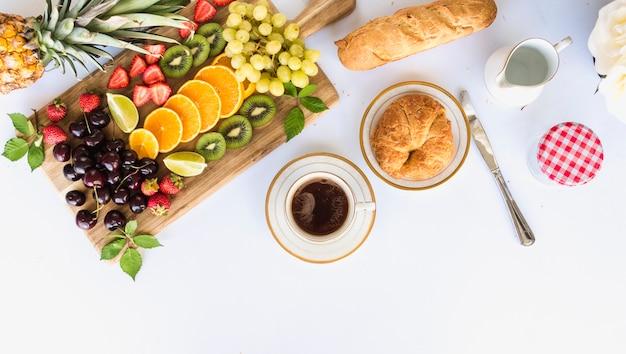 Obenliegende ansicht des gesunden frühstücks mit fruchtzusammenstellung, -tee und -brot