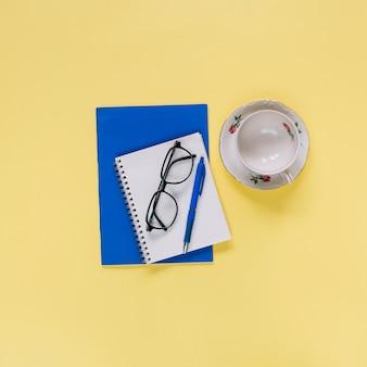Obenliegende ansicht des gewundenen notizblockes; tasse und brille auf gelber oberfläche