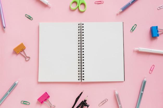 Obenliegende ansicht des gewundenen notizblockes umgeben durch verschiedene schreibwarengeschäfte auf rosa hintergrund