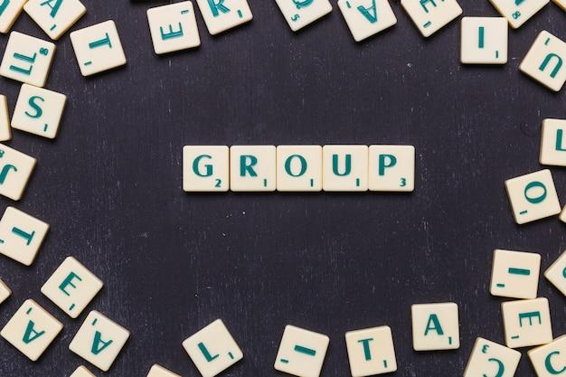 Obenliegende ansicht des gruppentextes auf scrabble-buchstaben über schwarzem hintergrund