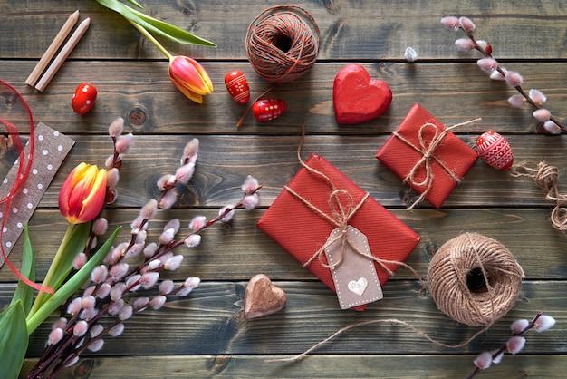 Obenliegende ansicht des holztischs mit frühjahrdekorationen, eingewickelten geschenken, weiden- und tulpenblumen und ostereiern