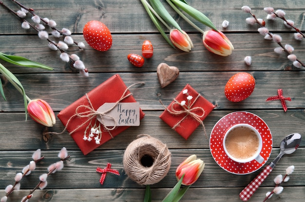 Obenliegende ansicht des holztischs mit frühjahrdekorationen, kaffeetasse, eingewickelten geschenken, blumen und ostereiern