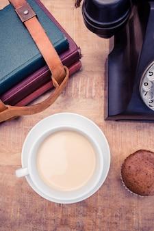 Obenliegende ansicht des kaffees mit altem überlandleitungstelefon und tagebüchern auf tabelle