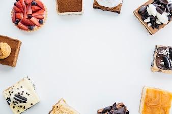 Obenliegende Ansicht des köstlichen Gebäcks Rahmen auf weißem Hintergrund bildend