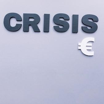 Obenliegende ansicht des krisenwortes mit eurozeichen auf grauem hintergrund