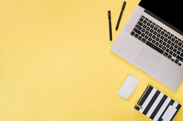 Obenliegende ansicht des laptops und der schreibwaren auf gelber oberfläche