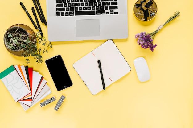 Obenliegende ansicht des laptops und des mobiltelefons mit briefpapier auf gelbem hintergrund